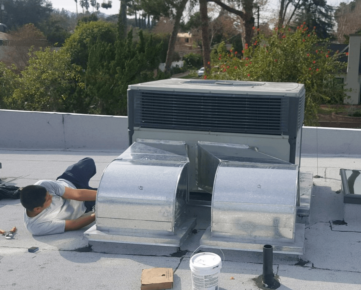 Mor Air staff on the ground working on an air conditioning unit outdoors